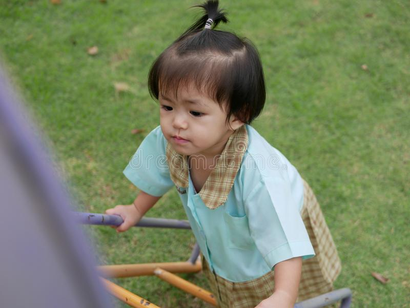 Little Asian baby girl enjoys climbing stairs at a playground. Ttle Asian baby girl, 18 months old, enjoys climbing stairs at a playground. - large muscle and royalty free stock photography