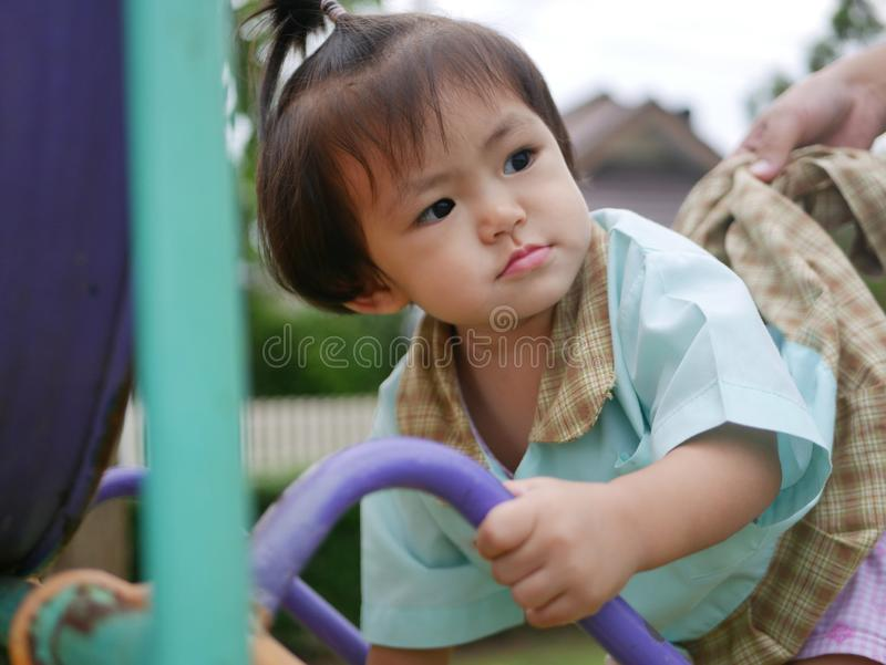 Little Asian baby girl enjoys climbing stairs at a playground. Ttle Asian baby girl, 18 months old, enjoys climbing stairs at a playground. - large muscle and royalty free stock images