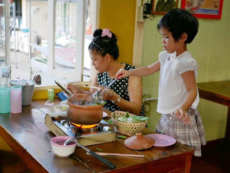Little Asian baby girl enjoys cooking a hot pot for her mother stock photos