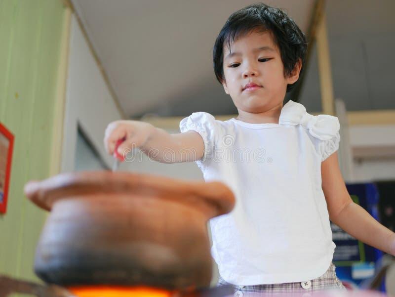 Little Asian baby girl enjoys cooking Thai-style hot pot stock photo