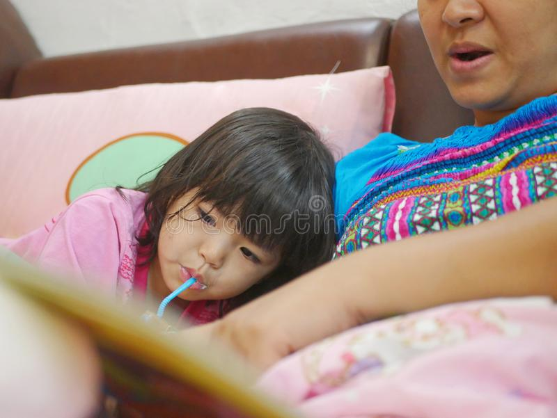Little Asian baby girl enjoys drinking milk and listening to her mother reading a fairy tale book before her bedtime stock photography