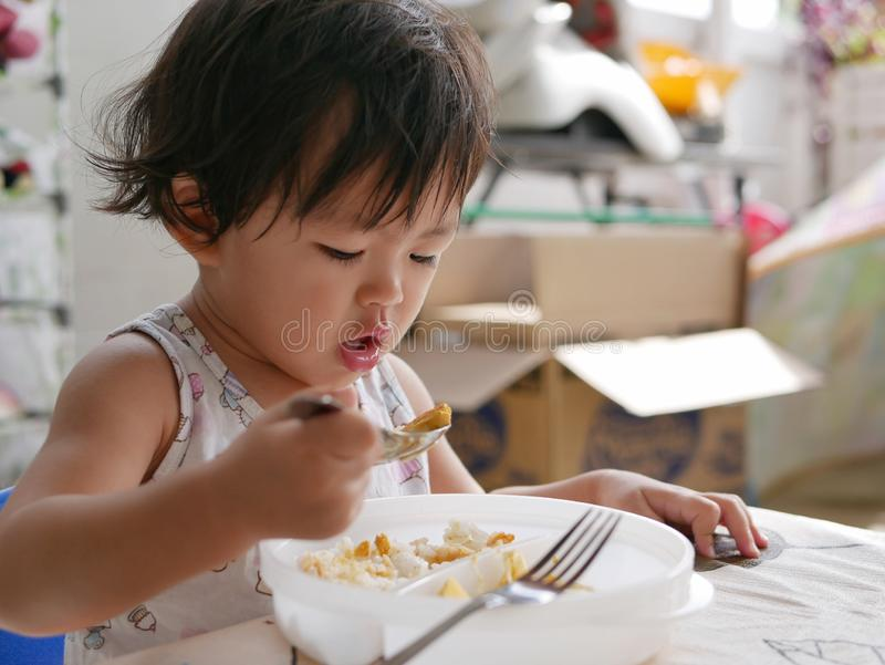 Little Asian baby girl enjoys eating food by herself. Child development by allowing them to do things by themselves royalty free stock photography