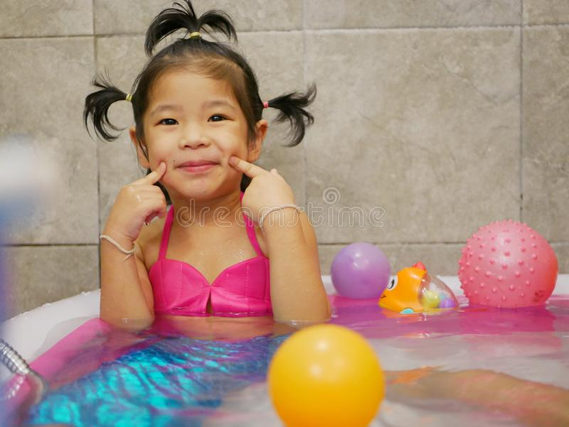 Little Asian baby girl enjoys getting dressed as a mermaid and playing water in a small pool at home royalty free stock images