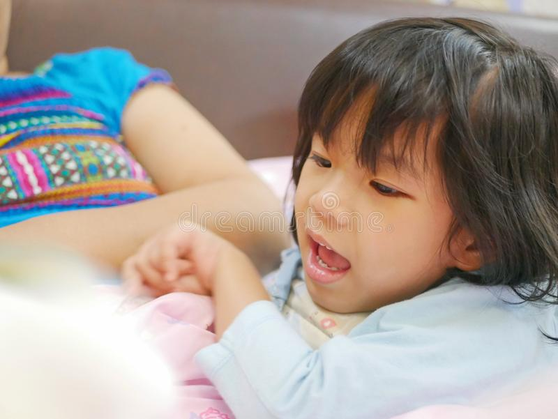 Little Asian baby girl enjoys listening to her mother reading a fairy tale book before her bedtime royalty free stock images