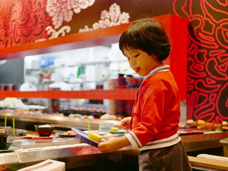 Little Asian baby girl enjoys picking raw ingredients, for hotpot cooking, serving on a moving conveyor belt. Little Asian baby girl enjoys picking raw royalty free stock photography