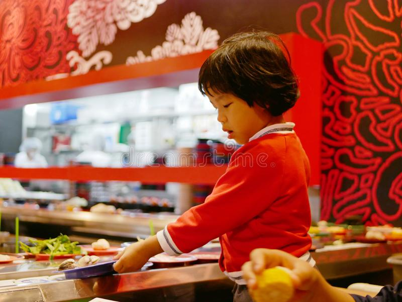 Little Asian baby girl enjoys picking raw ingredients, for hotpot cooking, serving on a moving conveyor belt. Little Asian baby girl enjoys picking raw royalty free stock images