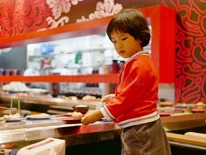 Little Asian baby girl enjoys picking raw ingredients, for hotpot cooking, serving on a moving conveyor belt. Little Asian baby girl enjoys picking raw royalty free stock photo