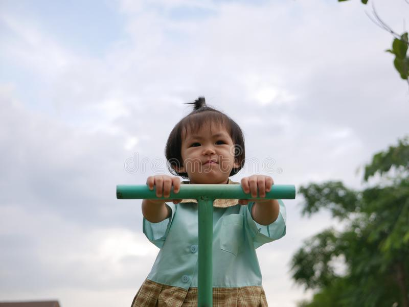 Little Asian baby girl enjoys playing a seesaw board. Ttle Asian baby girl, 18 months old, enjoys playing a seesaw board. - large muscle and motor development in stock image
