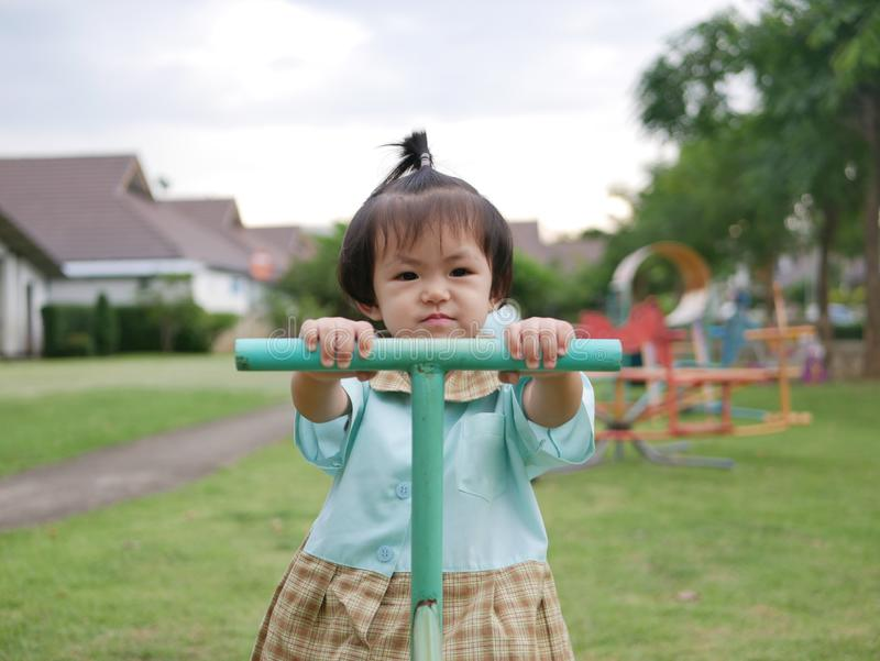 Little Asian baby girl enjoys playing a seesaw board. Ttle Asian baby girl, 18 months old, enjoys playing a seesaw board. - large muscle and motor development in royalty free stock photography