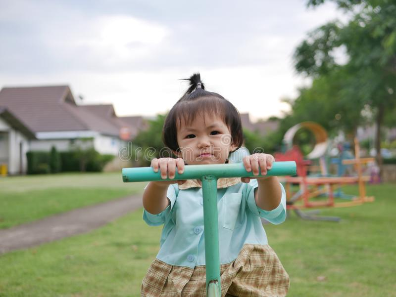 Little Asian baby girl enjoys playing a seesaw board. Ttle Asian baby girl, 18 months old, enjoys playing a seesaw board. - large muscle and motor development in stock photography