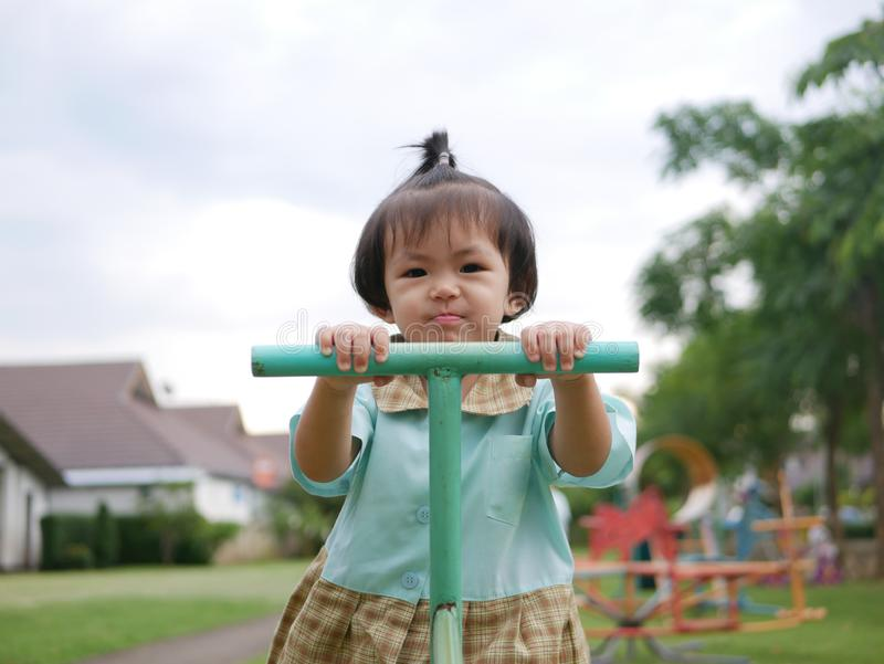 Little Asian baby girl enjoys playing a seesaw board. Ttle Asian baby girl, 18 months old, enjoys playing a seesaw board. - large muscle and motor development in stock photo