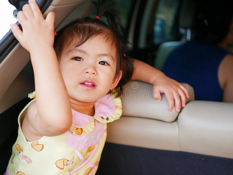 Little Asian baby girl enjoys staying in a car boot - baby being curious and exploring space around them. Little Asian baby girl, 24 months old, enjoys staying royalty free stock images