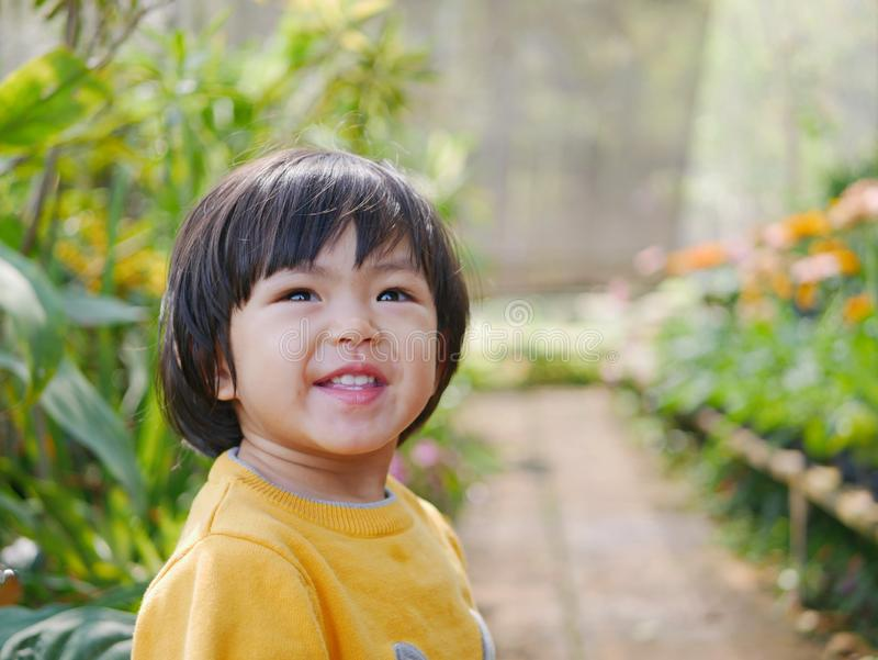 Little Asian baby girl enjoys staying inside a covered greenhouse flora garden. Little Asian baby girl, 24 months old, enjoys staying inside a covered greenhouse royalty free stock photo