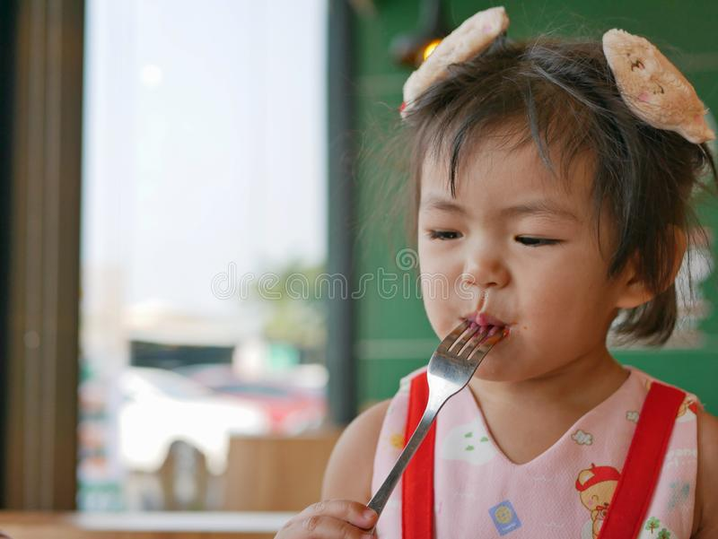 Little Asian baby girl enjoys tasting tomato ketchup by herself at a restaurant stock image