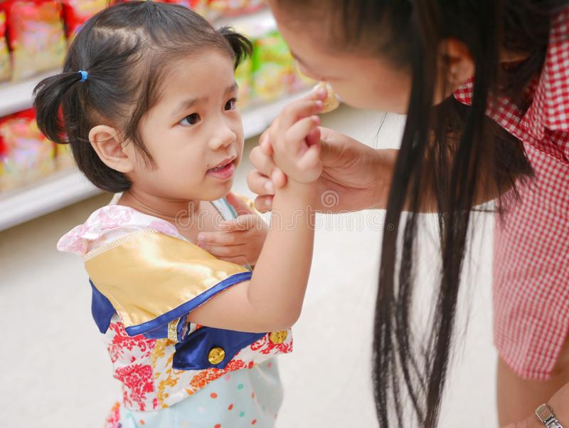 Little Asian baby girl feeding her mother a potato chip - children learn to give royalty free stock photo