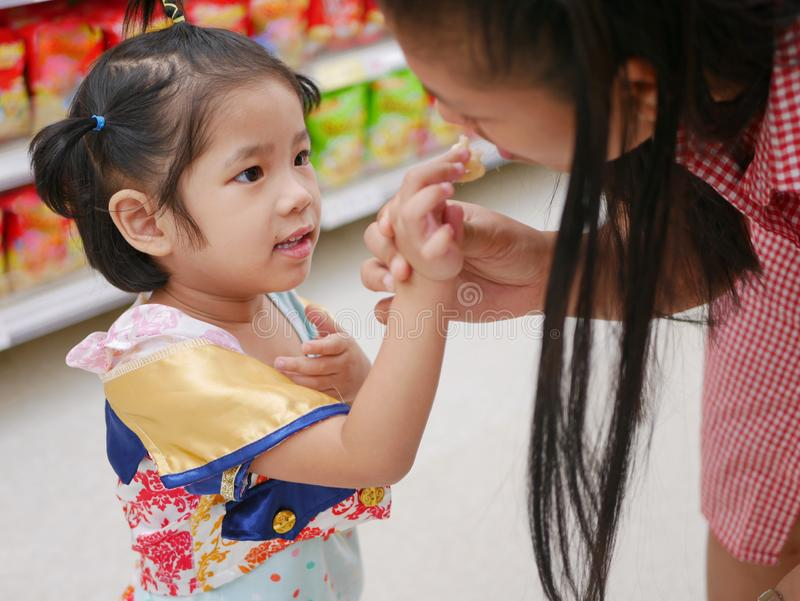 Little Asian baby girl feeding her mother a potato chip - children learn to give stock image