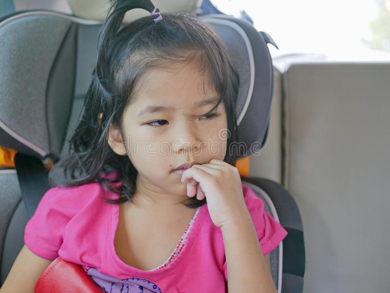 Little Asian baby girl feeling sleepy, sitting in a car seat, during a long trip.  stock photos