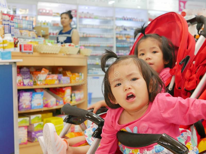 Little Asian baby girl front getting bored waiting for a long time in a baby stroller for her mother buying drugs a pharmacy stock image