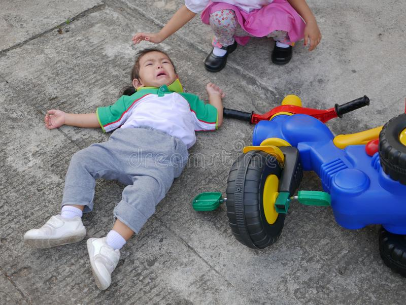Little Asian baby girl getting hurt and crying after falling from a bike - child accident royalty free stock photography