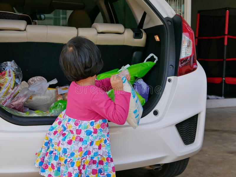 Little baby girl help carrying stuff from the back of the car into the house royalty free stock image