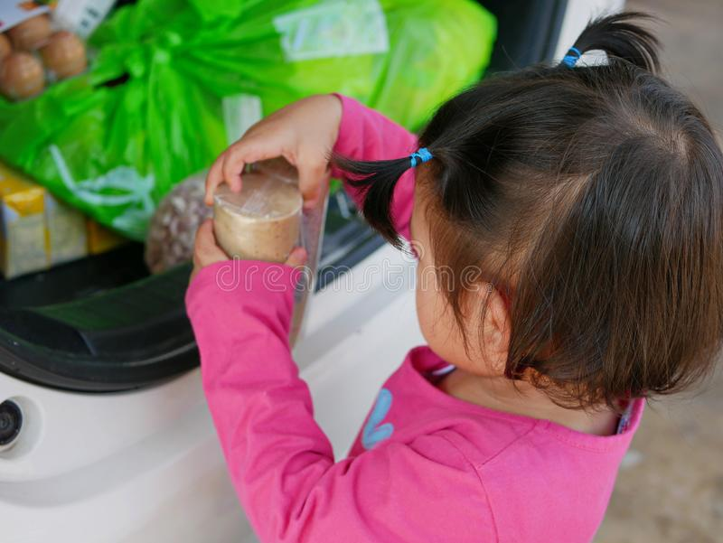 Little Asian baby girl help carrying stuff from the back of the car into the house royalty free stock photos