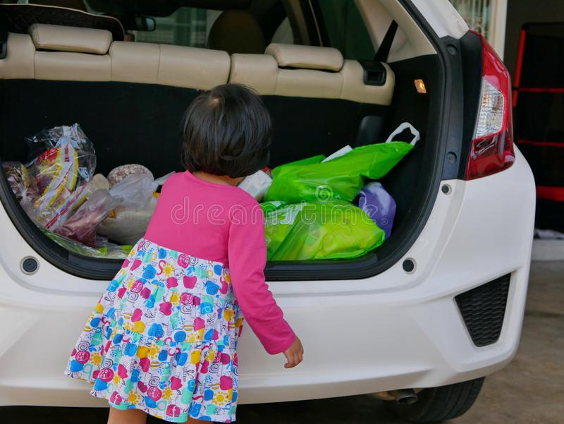 Little Asian baby girl help carrying stuff from the back of the car into the house royalty free stock image