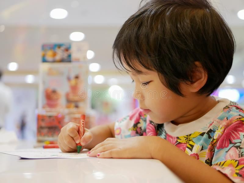 Little Asian baby girl learning to grasp a crayon and do painting by herself. Little Asian baby girl, 35 months old, learning to grasp a crayon and do painting royalty free stock photography