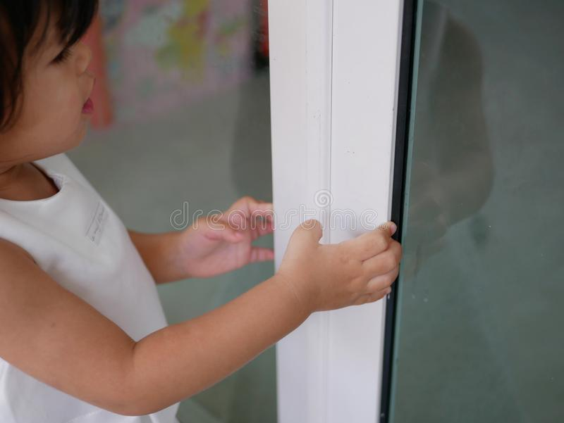 Little Asian baby girl learning to shut / close sliding door by herself royalty free stock images