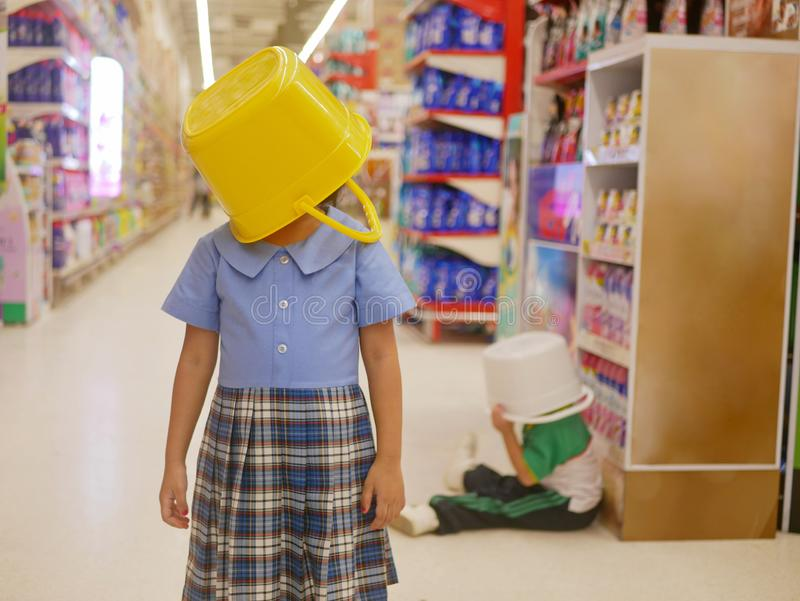 Little Asian baby girl left covering her head with a yellow plastic bucket, playing with her sister, at supermarket stock photos