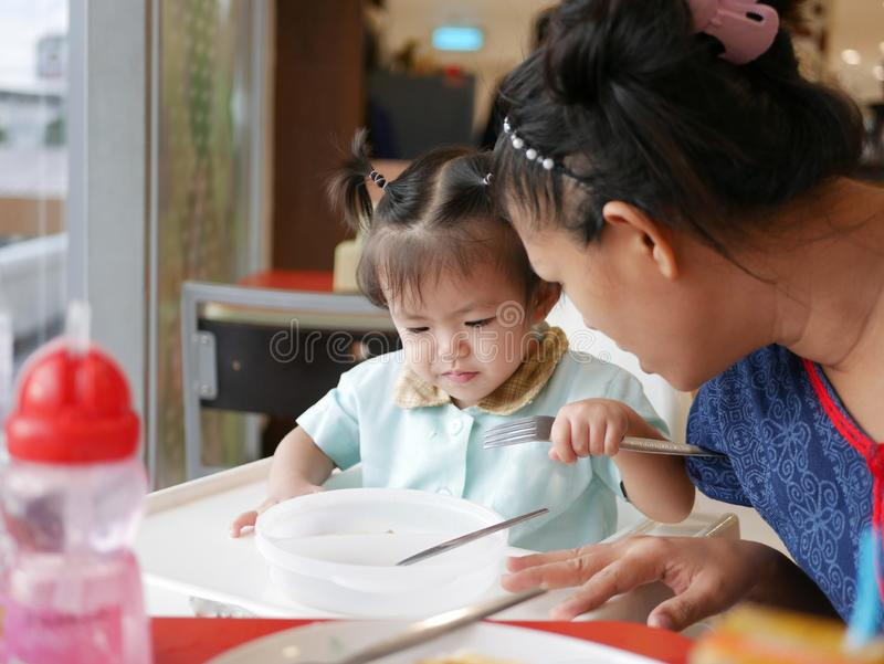 Little Asian baby girl listening to her mother explaining how to eat with fork and spoon by herself stock image