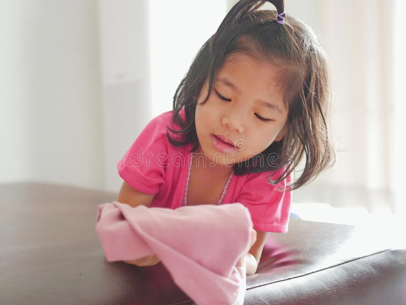Little Asian baby girl looking at the her pants / work in her hands, as she just successfully folded it royalty free stock image