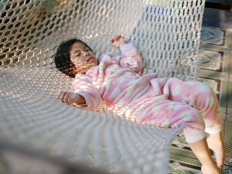 Little Asian baby girl comfortably lying down on a hammock with the morning sunlight royalty free stock image