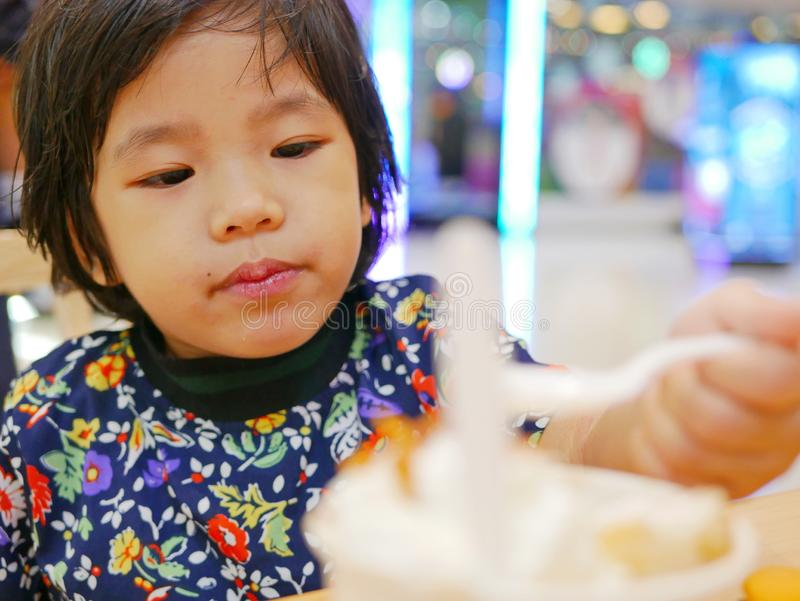 Little Asian baby girl enjoys having bread with ice cream by herself royalty free stock photos
