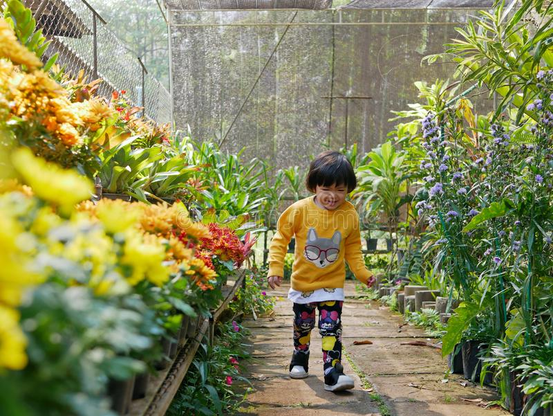 Little Asian baby girl enjoys walking in a flora garden - engaging with nature provides positive impact. Little Asian baby girl, 24 months old, enjoys walking in royalty free stock image