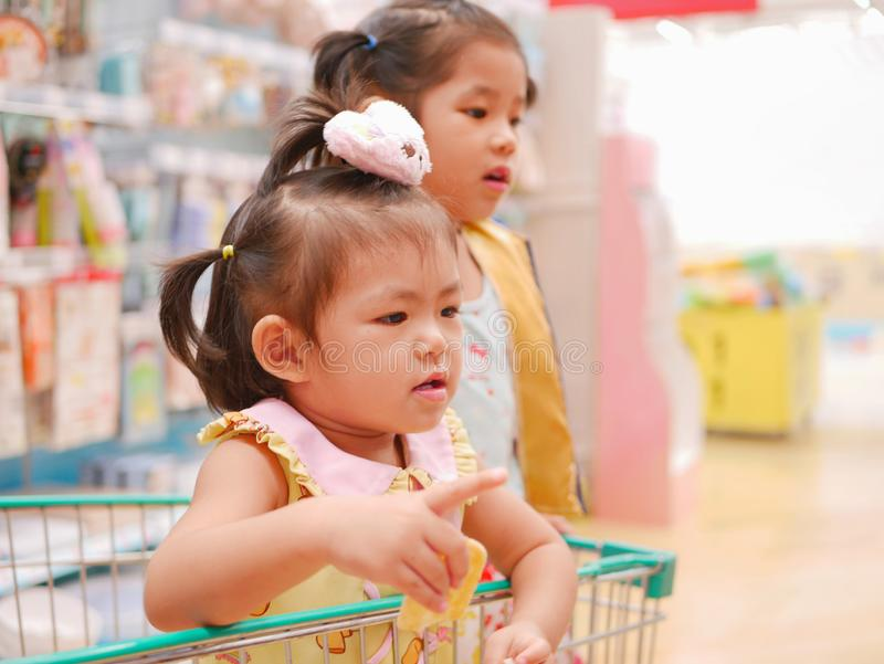 Little Asian baby girl having fun standing in a shopping cart with her sister seeing many products for sale royalty free stock image