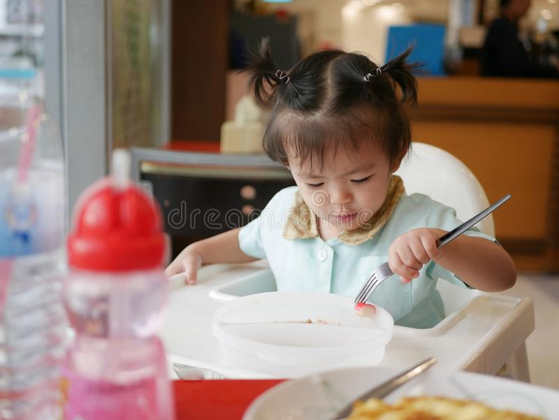 Little Asian baby girl learning to eat with fork by herself herself - ba stock photos