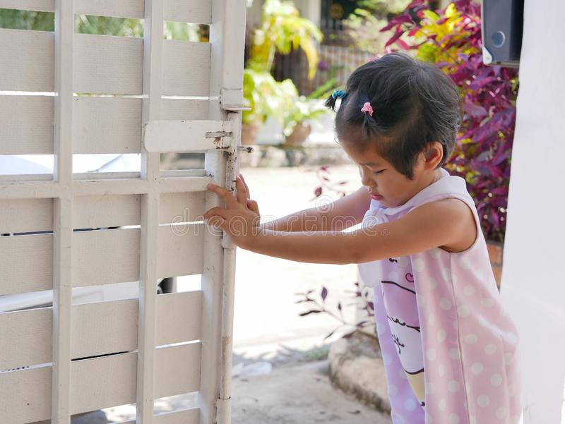 Little Asian baby girl learning to open front gate of a house by herself stock photography