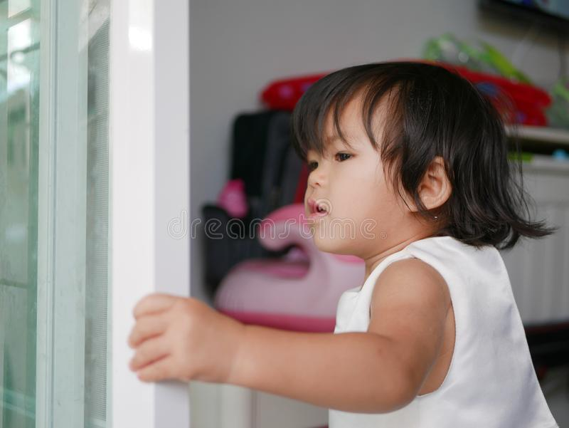 Little Asian baby girl learning to shut / close sliding door by herself stock photography