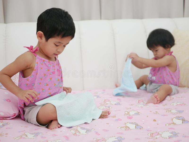 Little Asian baby girl left learning to fold clothes royalty free stock images