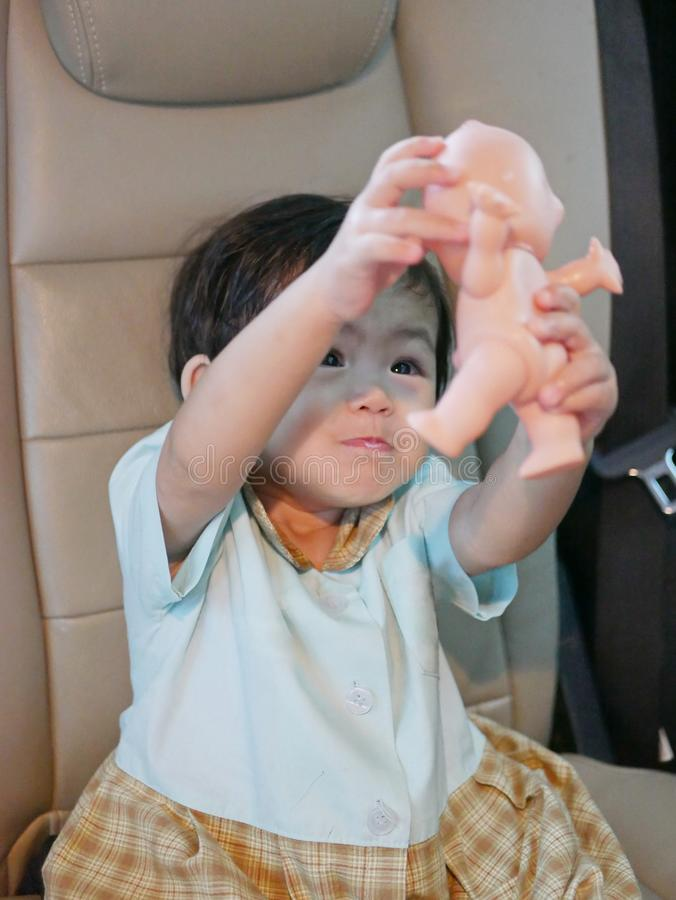 Little Asian baby girl lifting and doing a pretend play with a doll stock photography