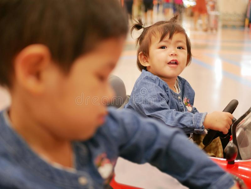Little Asian baby girl, 17 months old, right holding a steering wheel of a mini car stock images