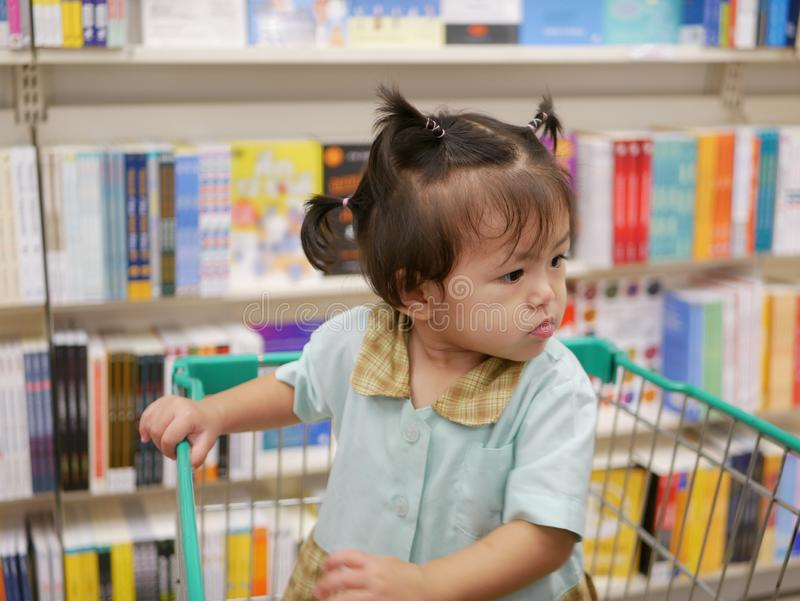 Little Asian baby girl in a shopping trolley being excited at books around her royalty free stock photo