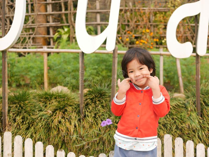 Little Asian baby girl, 38 months old, smiling and making a cute funny gesture.  royalty free stock image