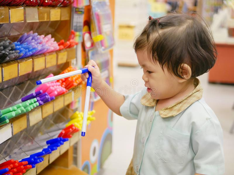 Little Asian baby girl taking color pens from the shelves. Little Asian baby girl, 18 months old, taking color pens from the shelves in a stationary shop royalty free stock image
