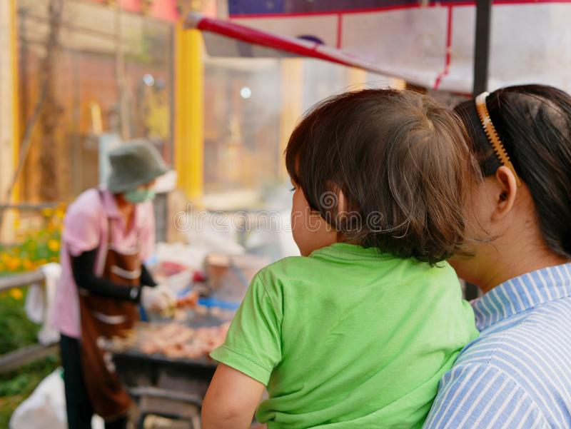 Little Asian baby girl together with her mother watching a female food vender selling street food royalty free stock images