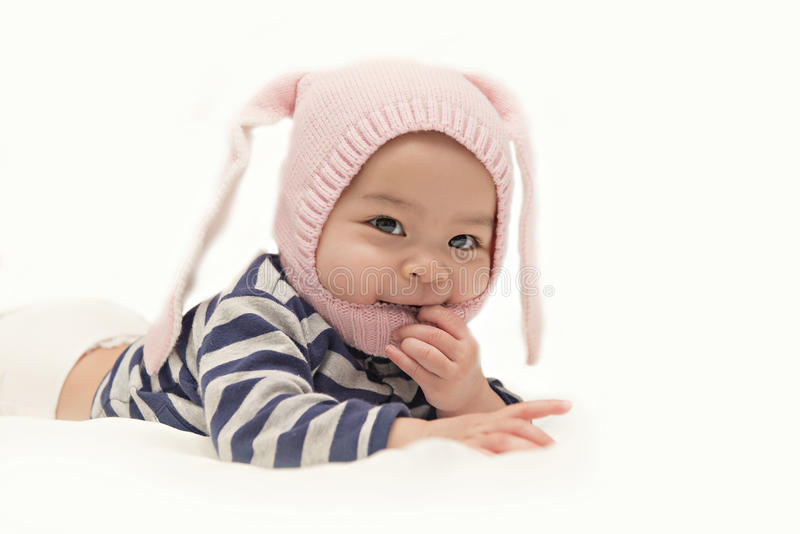 Little Asian baby girl with pink rabbit hat and sucks fingers on white background. Charming child. Little Asian baby girl with pink rabbit hat and sucks fingers royalty free stock photos