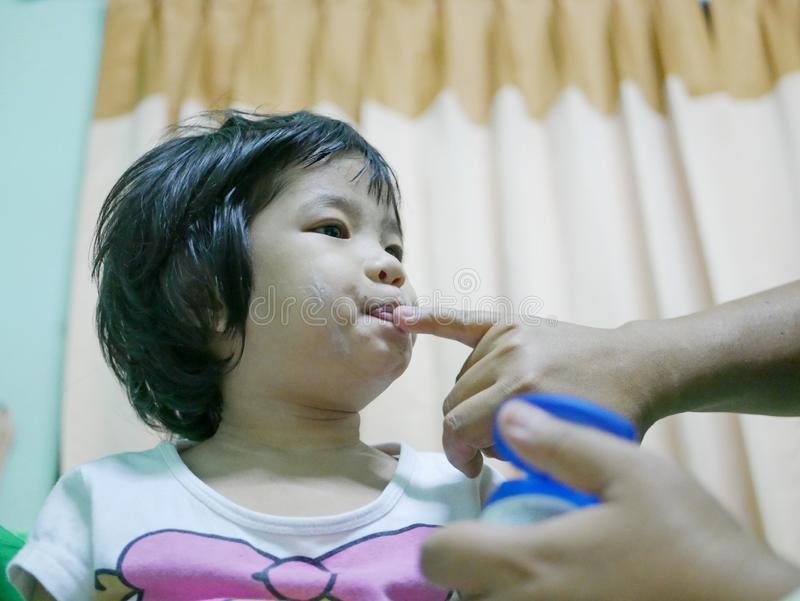 Little Asian baby girl, pressing her lips together while her mother applying petroleum jelly to moisturize them stock images