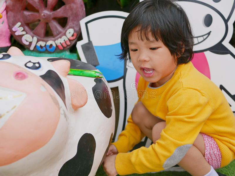 Little Asian baby girl pretends to milk a cow by hands - baby`s development through a pretending role play. During their early childhood stock photos