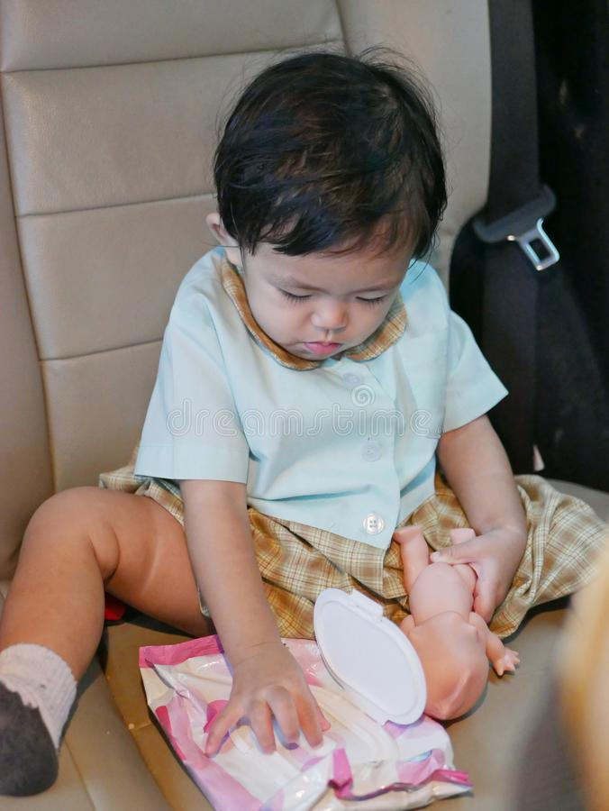 Little Asian baby girl pulling baby wipes out to clean away poo pretend play stock photography