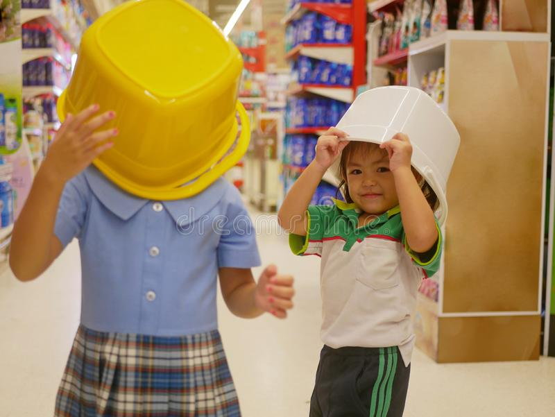 Little Asian baby girl right covering her head with a white plastic bucket, playing with her sister, at supermarket stock photos